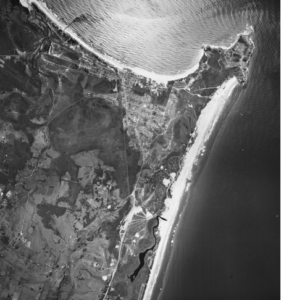 """1966 air photo of Byron Bay. NSW Govt Image. It shows Byron Bay at the peak of its industrial development, just as Wategos is being opened but before the Arts and Industrial, Sunrise Beach, Sandhills and Pacific Vista Estates and Suffolk Park are developed. Look closely at the image and you will notice a """"slick"""" of meatworks waste extending eastwards from the new jetty to Cape Byron. Sand mining has yet to commence behind Main Beach but dredges are active at Cosy Corner and what becomes Red Devils sports field and the High School. Previously mined areas are the white patches inland from the beaches. Tallow Creek retains its original form. The mineral sand processing plant can be seen on the site that becomes Woolworths. NORCO's butter factory appears at the southern end of Jonson Street. NORCO's piggery, is now the Arts factory,"""
